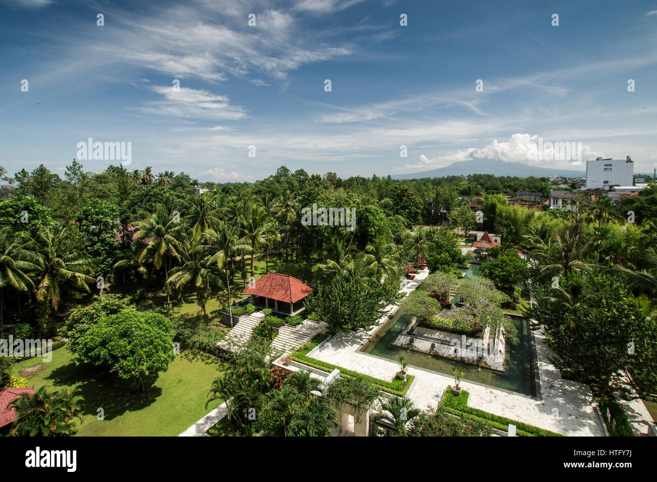 Cloud covered volcanoes Mount Merapi and Mount Sumbing seen from a hotel balcony in central Yogyakarta, Indonesia - Stock Image