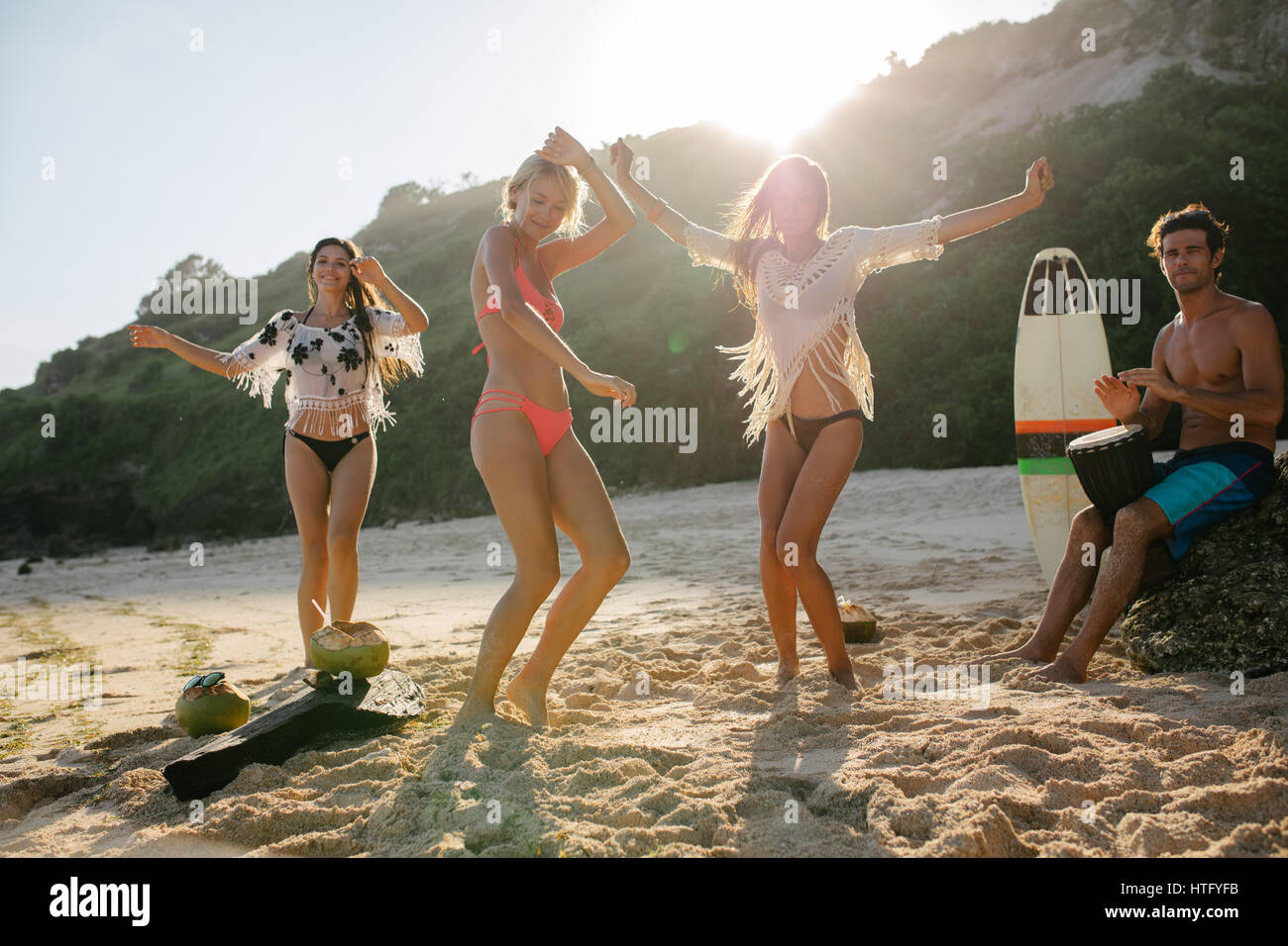 Happy friends enjoying on the beach and dancing. Young people having fun at beach party, women dancing and man playing - Stock Image