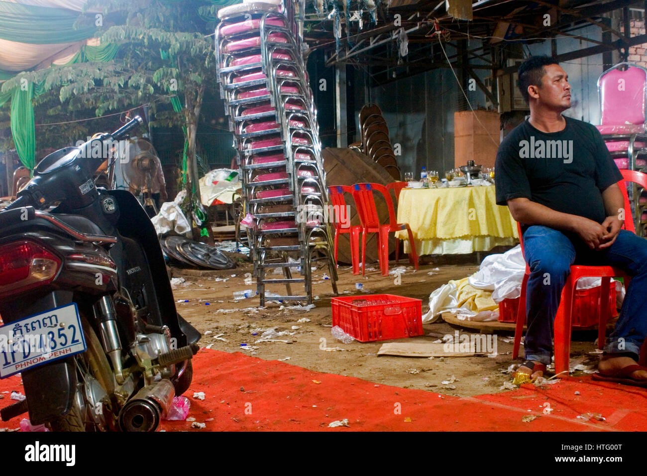 A man is sitting in a littered are near a stack of chairs after a wedding reception in Chork Village, Cambodia. - Stock Image