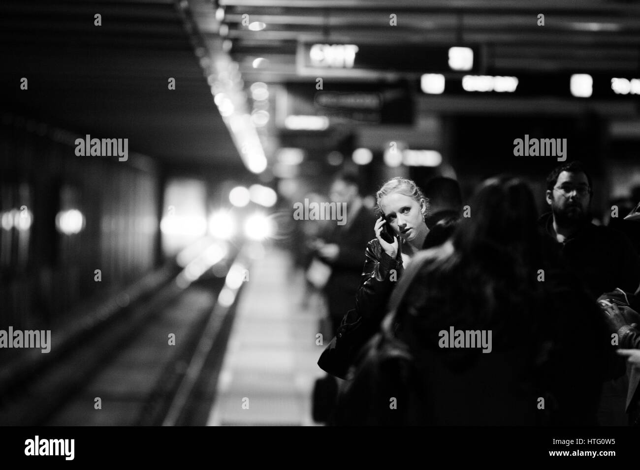 Woman standing among subway commuters talking on her cell phone. - Stock Image