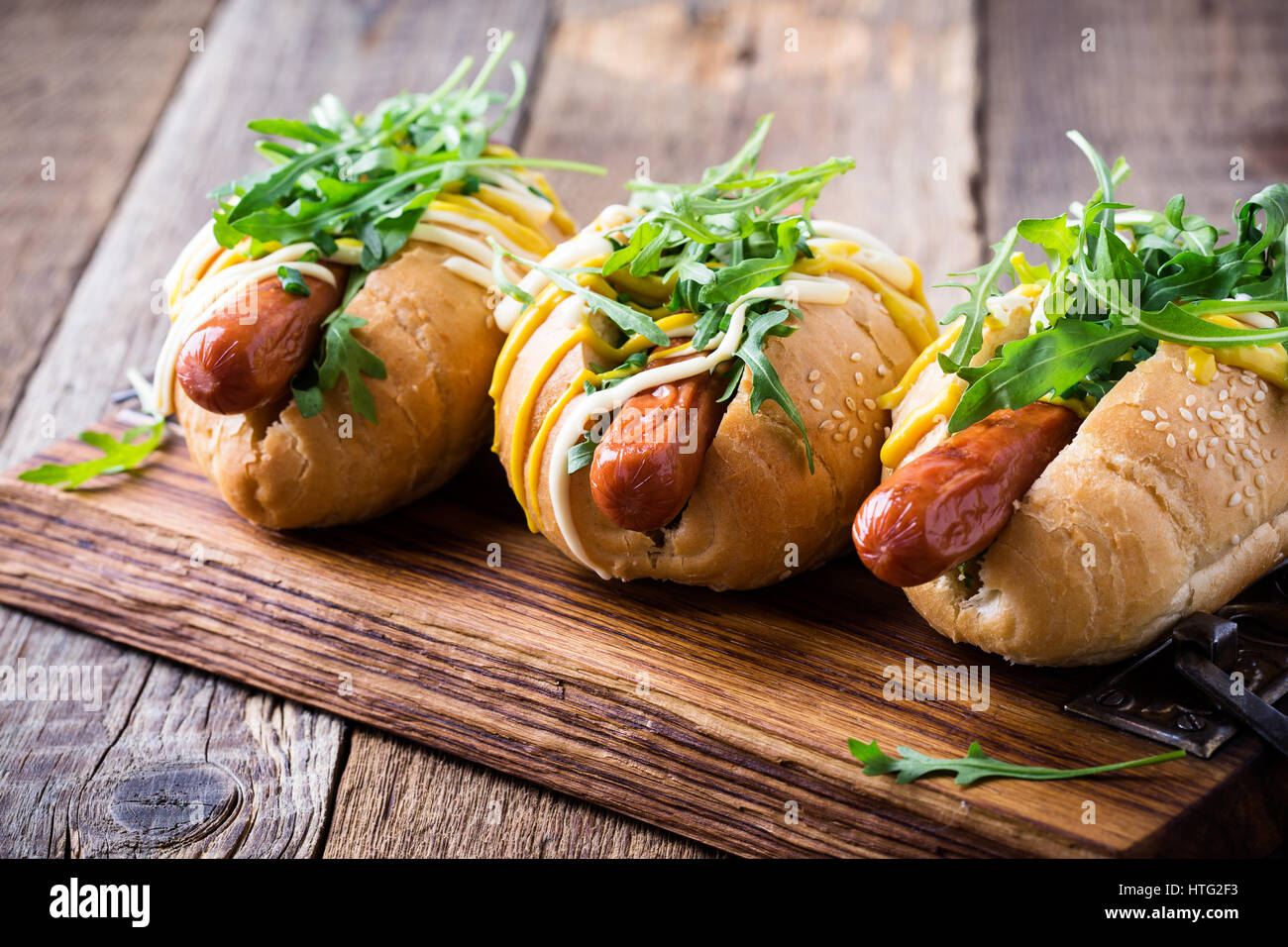 Beef hotdog on a bun with mustard and mayonnaise, topped with arugula on rustic wooden table, close up, selective - Stock Image