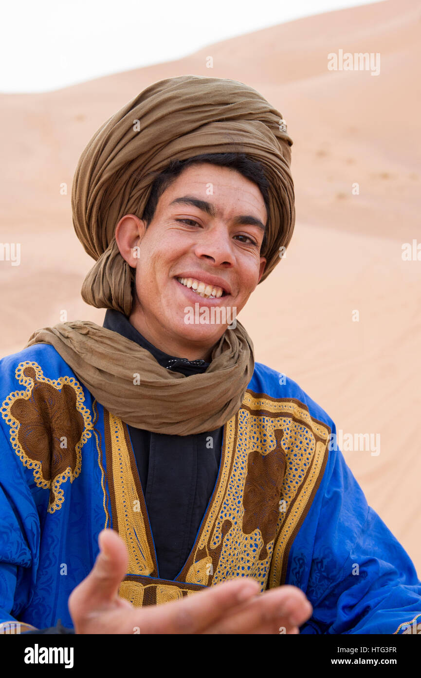 A nomadic Berber man with arms open welcoming tourists to the Sahara Desert, Morocco - Stock Image