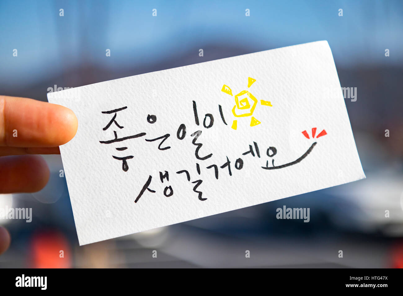fingers hold the korean language calligraphy : 'something good will happen.' - Stock Image