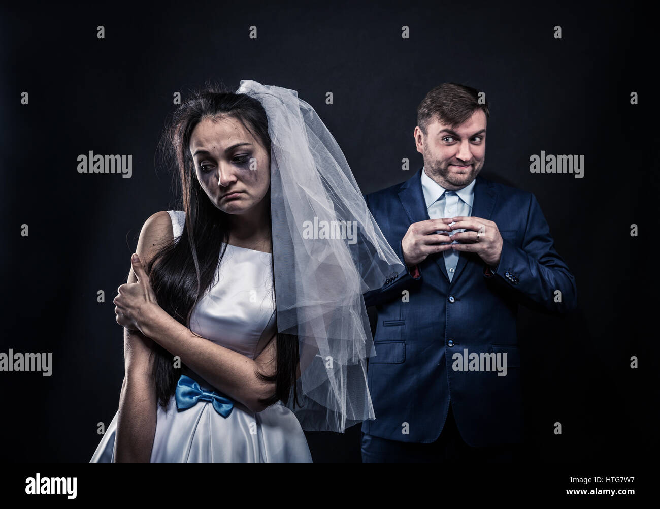 Bride with tearful face, groom with sly smile on background. Unhappy marriage - Stock Image