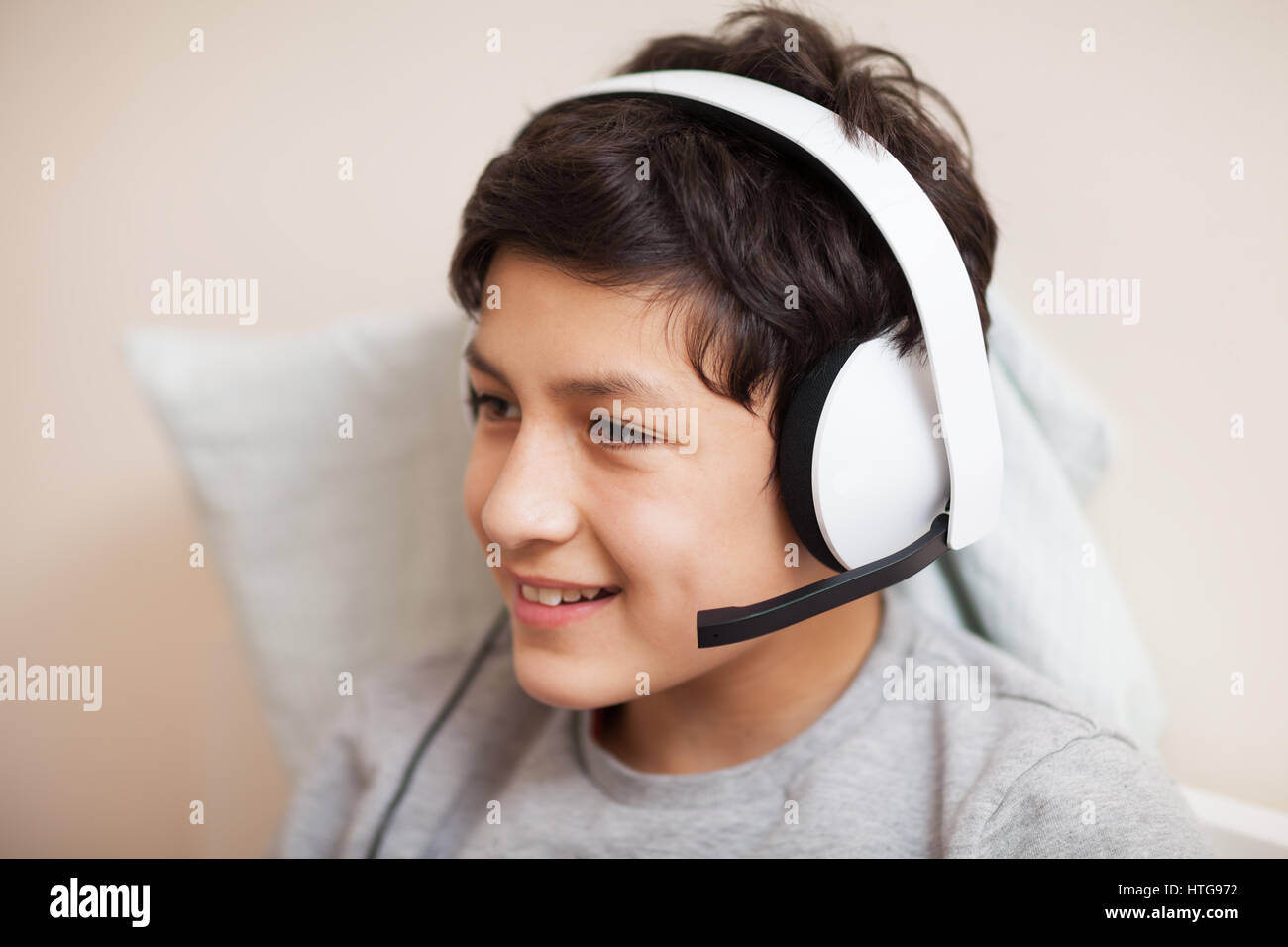 Boy playing on-line with friends - Stock Image