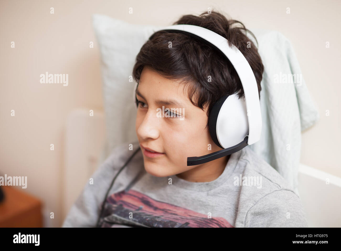 Young boy playing on-line with friends - Stock Image