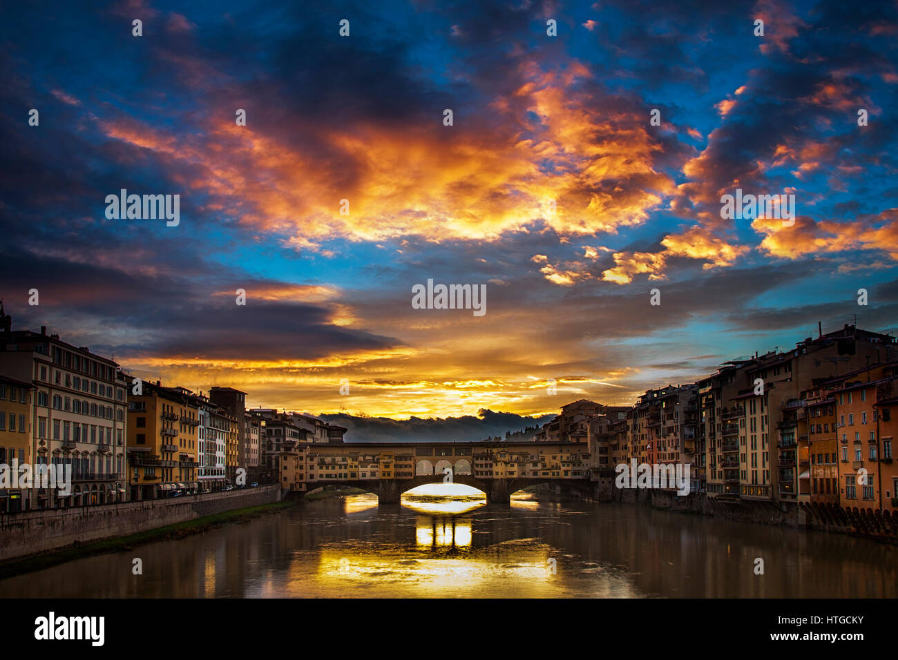 Clearing storm clouds at dawn create a dramatic sunrise over the Ponte Vecchio bridge in Florence, Italy - Stock Image