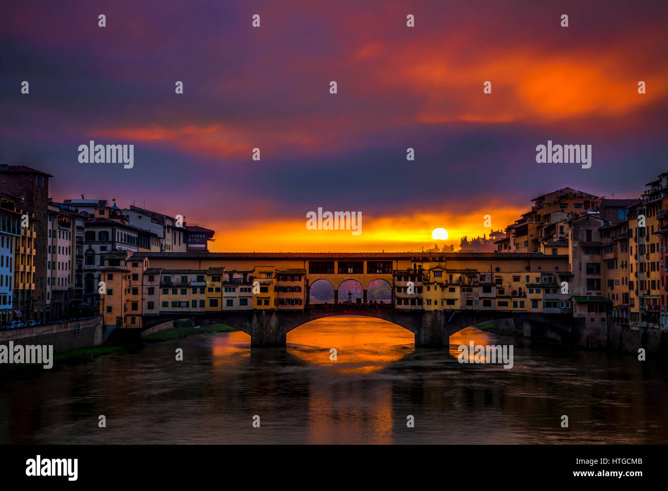 Clearing storm clouds at dawn create a dramatic sunrise over the Ponte Vecchio bridge in Florence, Italy with the - Stock Image
