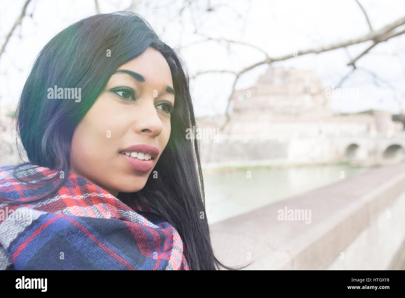 Young beautiful mixed race woman with melancholic expression, looking over, in Rome, Italy with Sant Angelo Castle - Stock Image