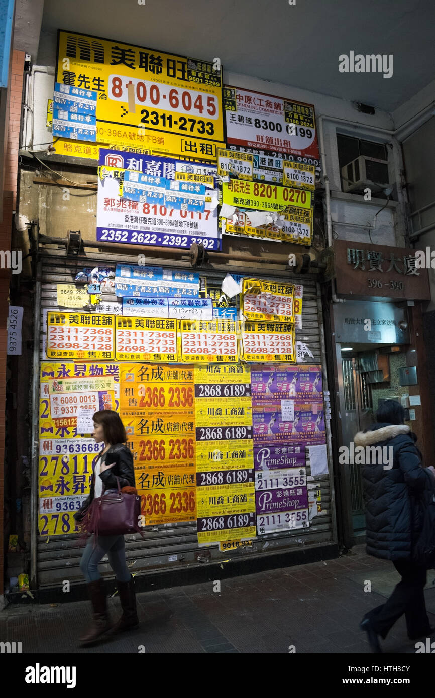 Property ads covering front of empty retail store in Hong Kong - Stock Image