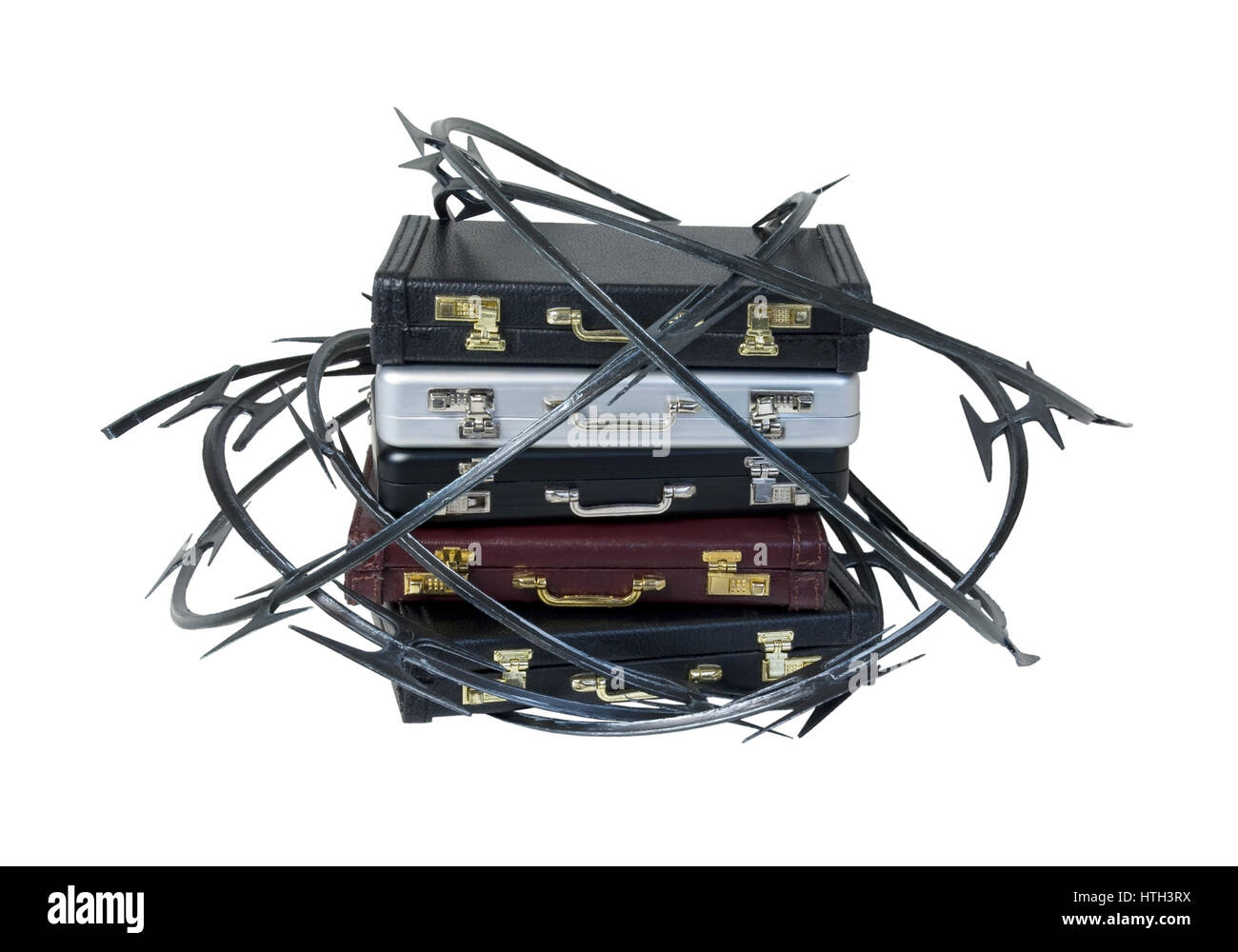 Sharp razor wired used as a barrier around a stack of briefcases - path included Stock Photo