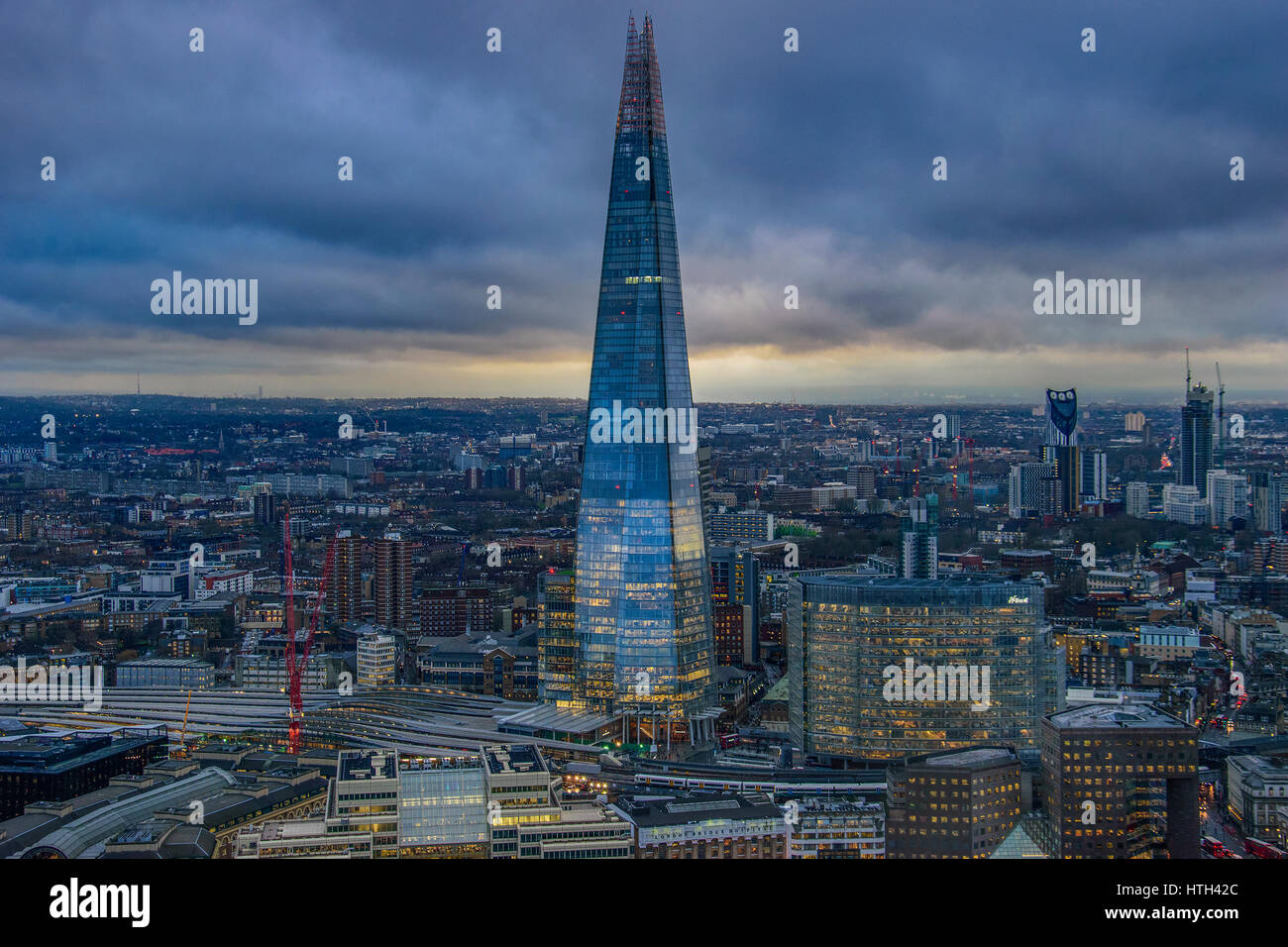 Panoramic aerial view of urban London with the Shard skyscraper and Thames river at sunset against a cloudy sky. Stock Photo