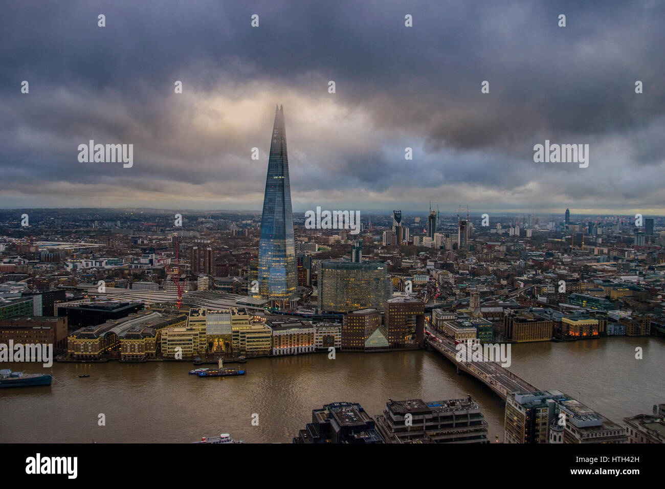 Panoramic aerial view of urban London with the Shard skyscraper and Thames river at sunset against a cloudy sky. - Stock Image