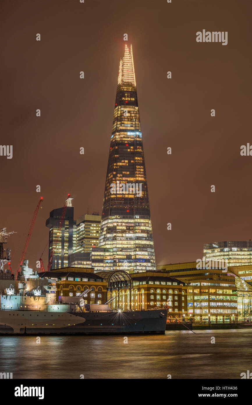 Night scene of urban London with the Shard skyscraper and Thames river at sunset against a cloudy sky. London, United Stock Photo