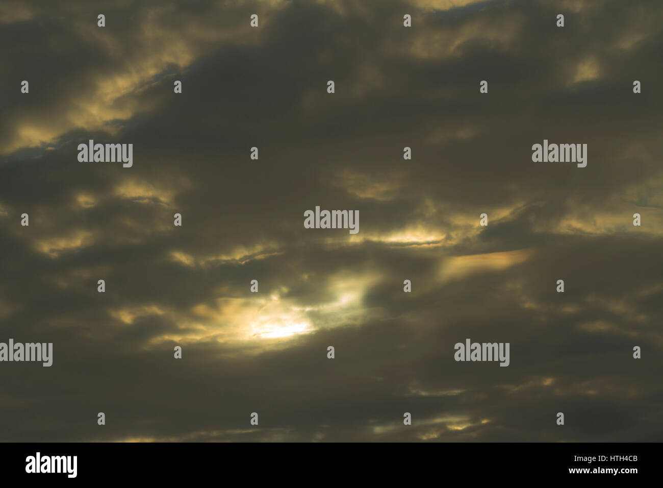 Dark clouds with the sun peeping through - Stock Image