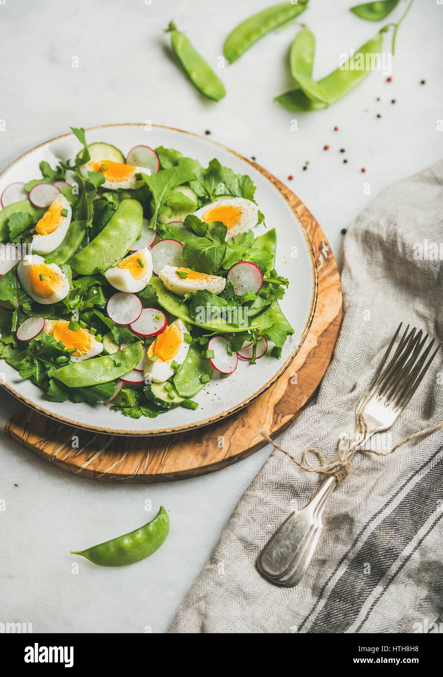 Healthy salad with radish, boiled egg, arugula, green pea, mint - Stock Image