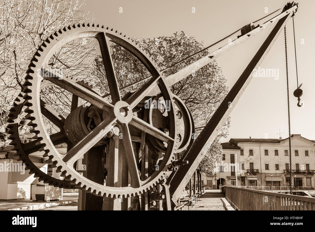 Gear wheels of an old and vintage crane. The crane is located near the small harbor on the lakeside of Luino, Lake - Stock Image