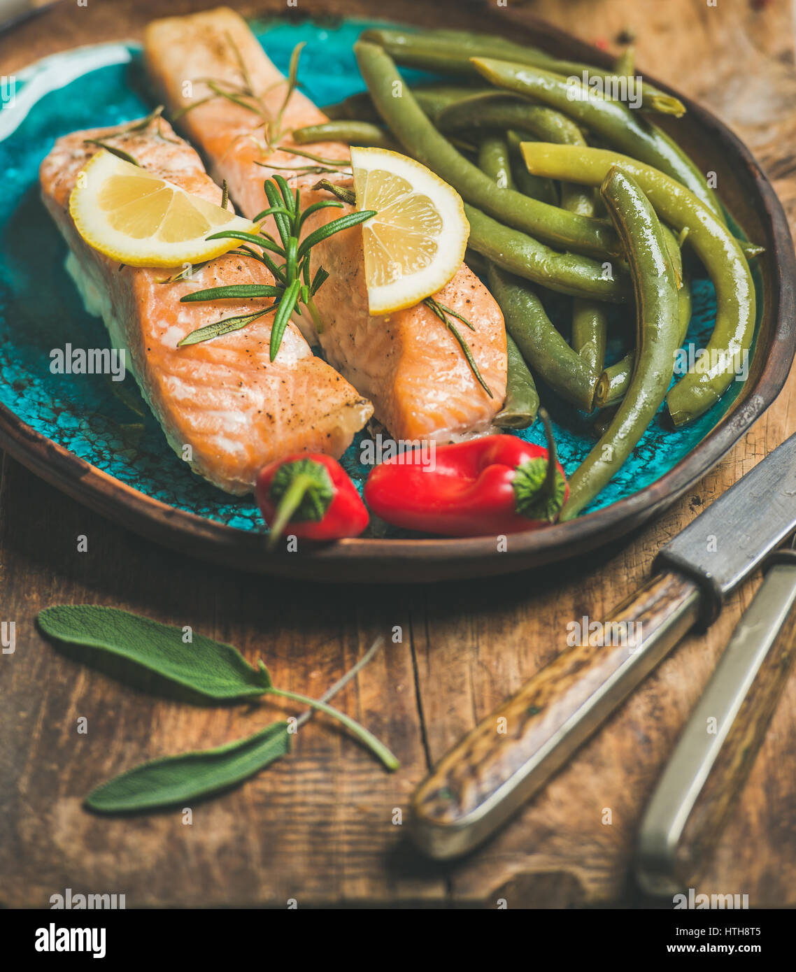 Roasted salmon with lemon, rosemary, chilli pepper and beans - Stock Image