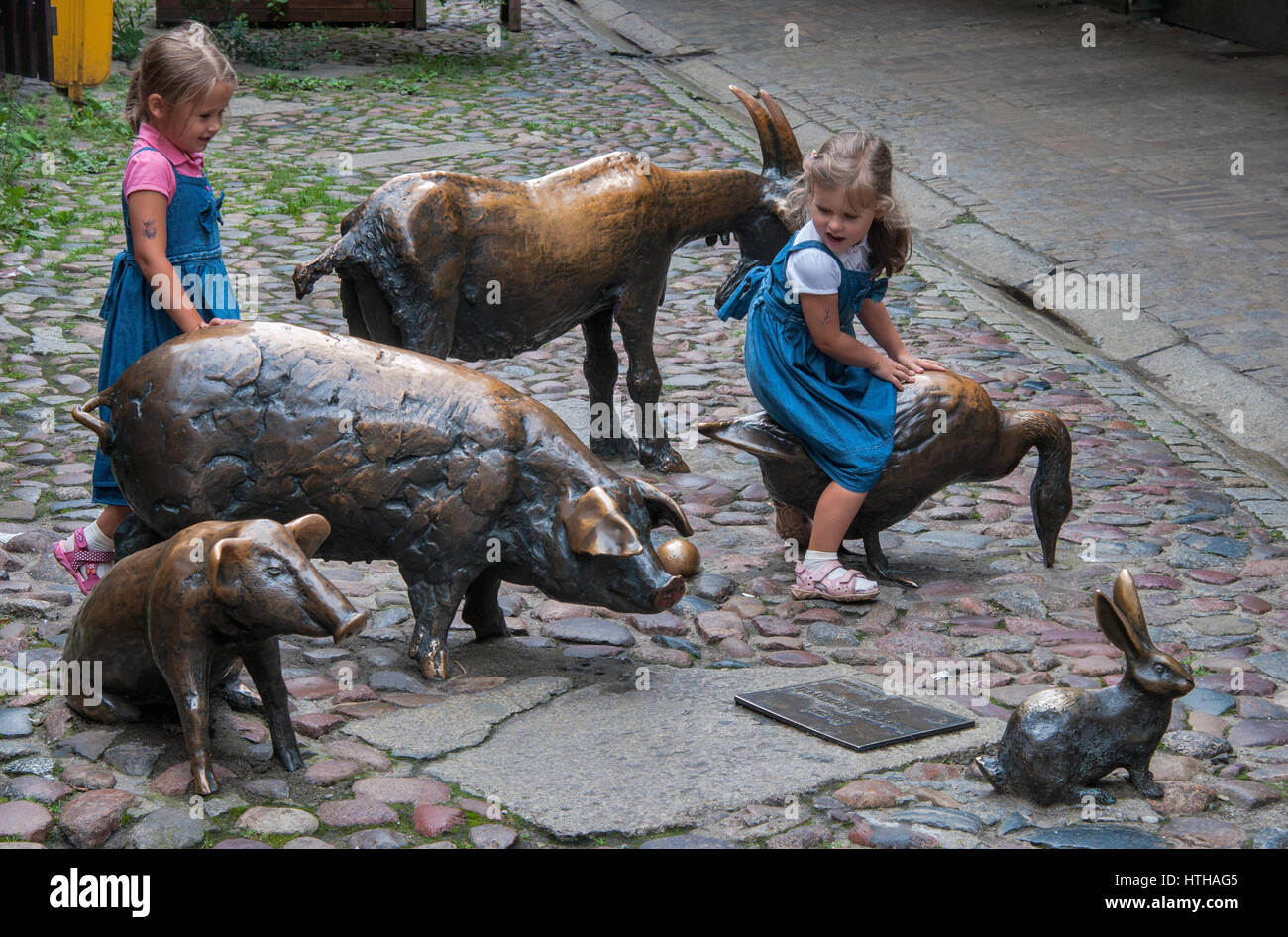 Two girls at sculptures 'In Honor of Animals for Slaughter' at Jatki passage. where medieval slaughter-houses - Stock Image