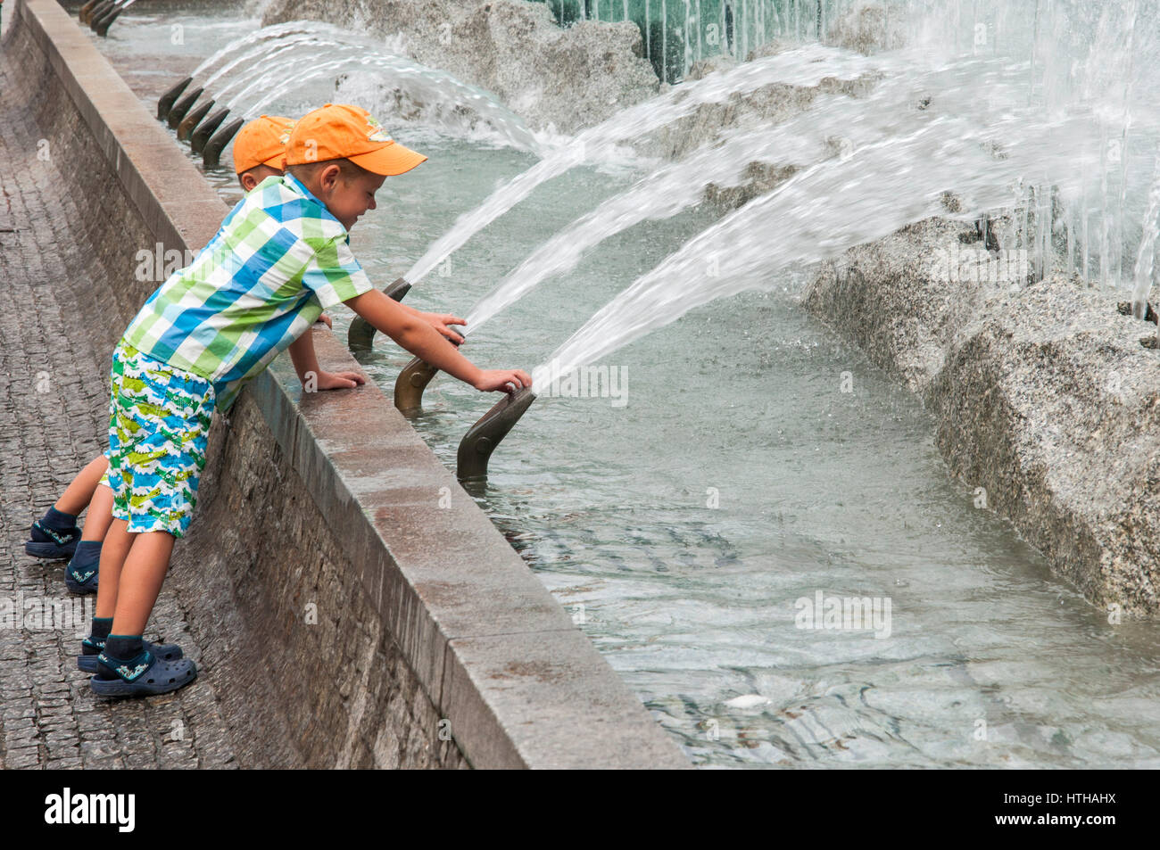 Two boys playing with water jets at Rynek Fountain, 1996, designed by Alojzy Gryt, at Rynek (Market Square) in Wroclaw, - Stock Image