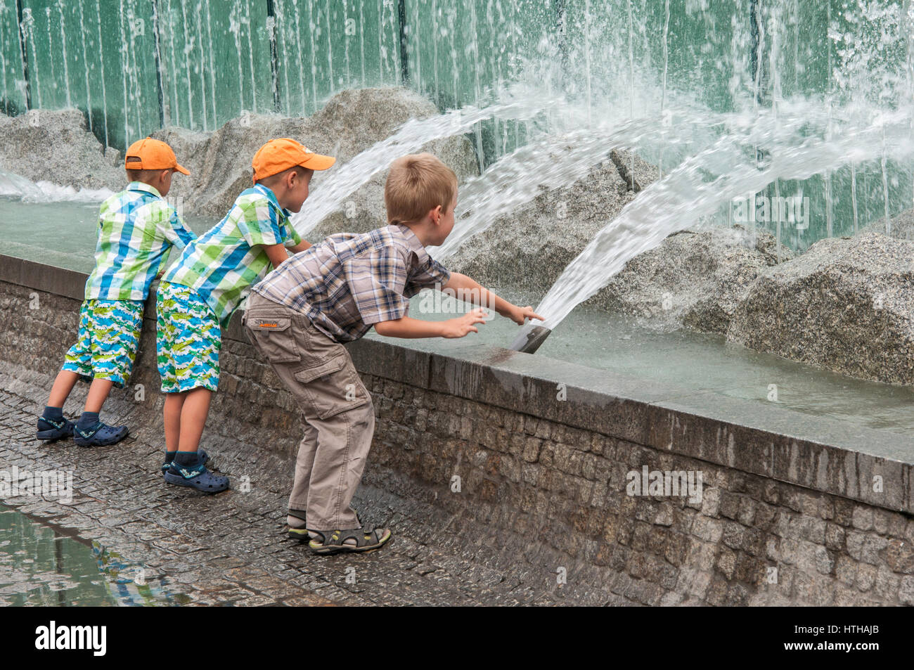 Three boys playing with water jets at Rynek Fountain, 1996, designed by Alojzy Gryt, at Rynek (Market Square) in - Stock Image