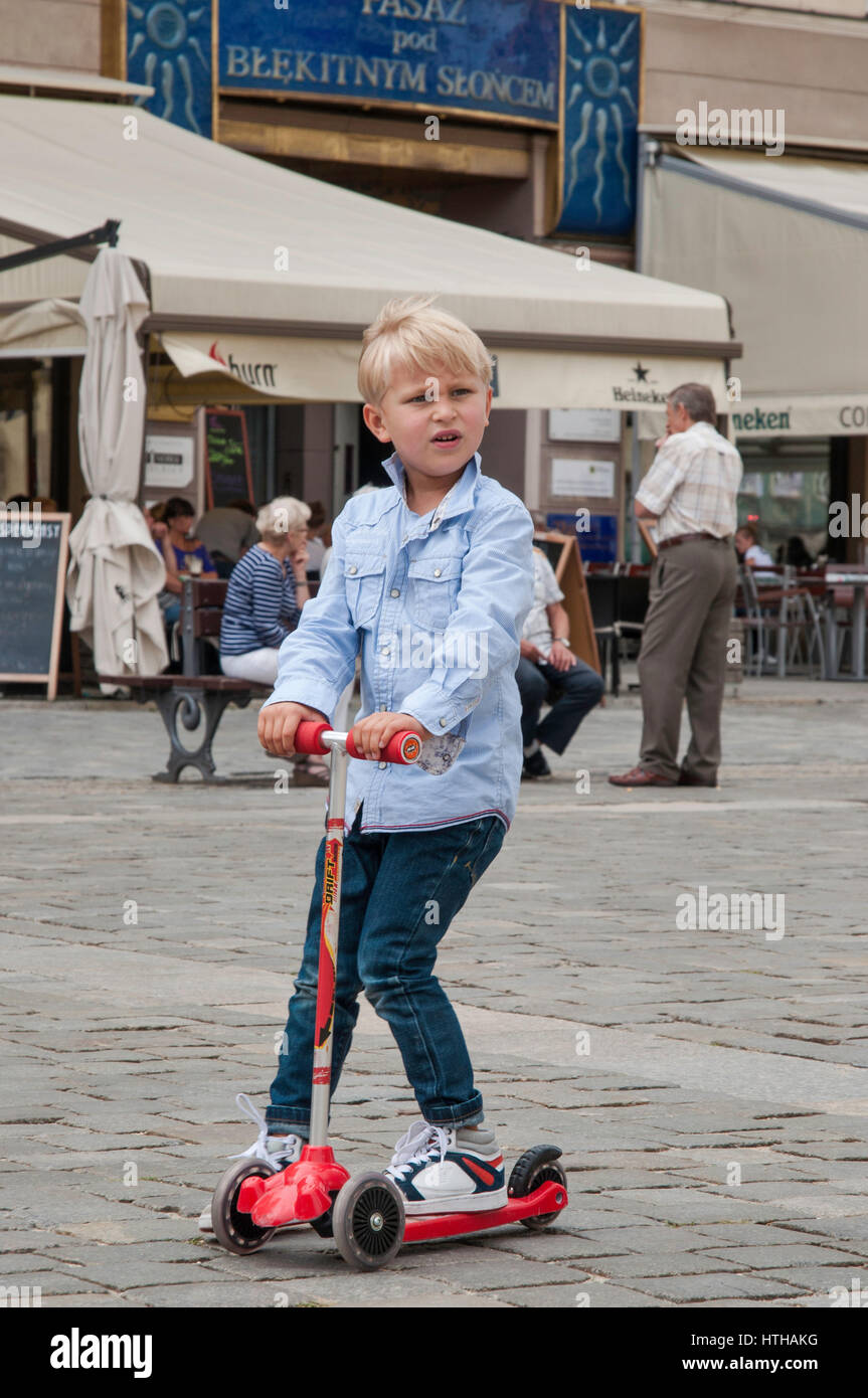 Boy on scooter, at Rynek (Market Square) in Wroclaw, Lower Silesia, Poland - Stock Image