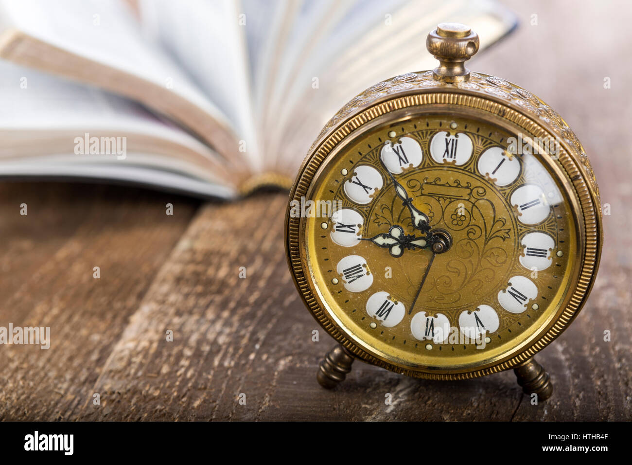 Holy Bible and gold alarm clock on wood table - Stock Image