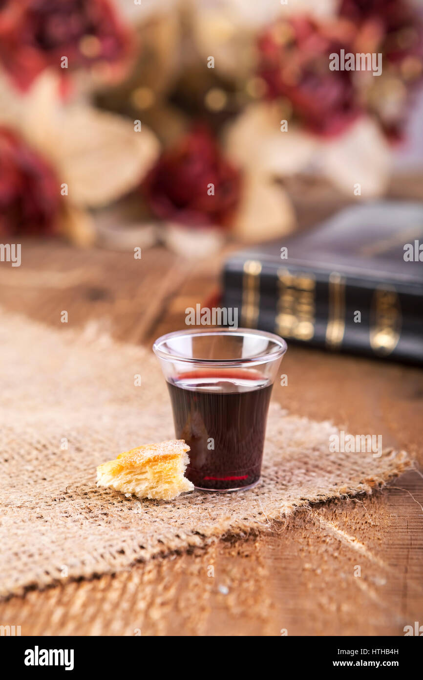 Taking Communion. Cup of glass with red wine, bread and Holy Bible on wooden table close-up. Focus on glass - Stock Image
