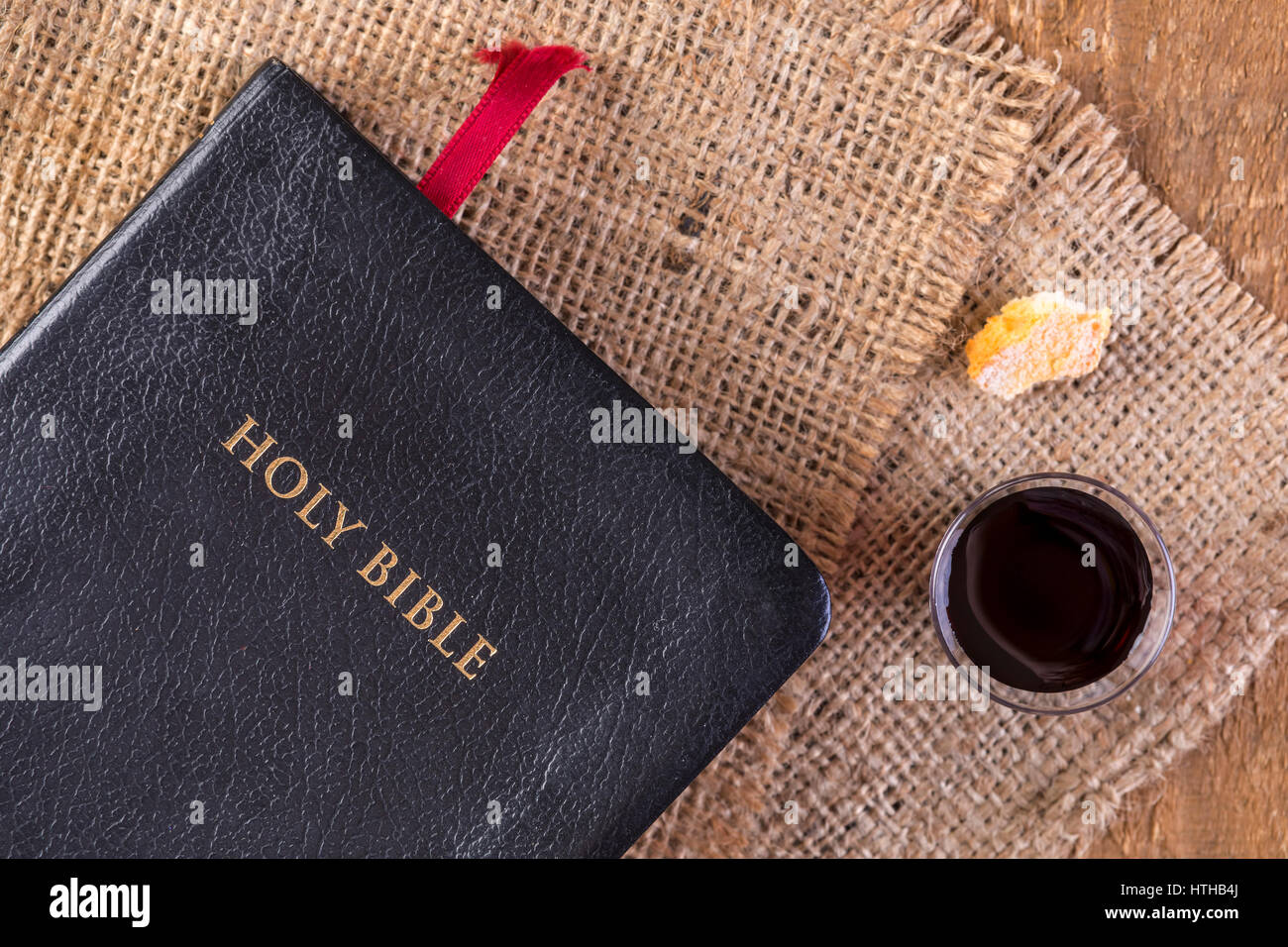 Taking Communion. Cup of glass with red wine, bread and Holy Bible on wooden table close-up - Stock Image