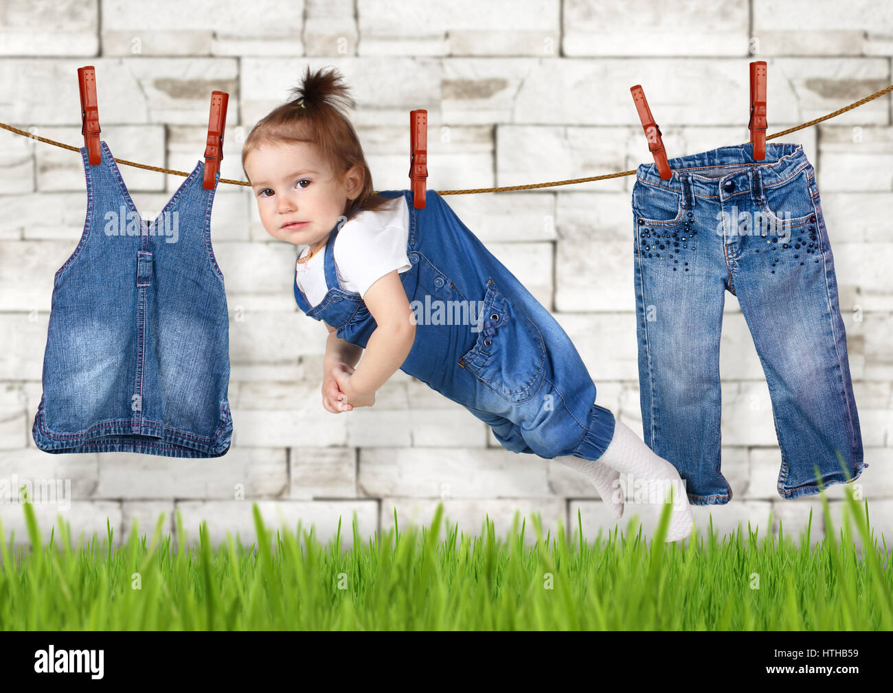 failed housework concept, Funny child hanging on clothesline - Stock Image