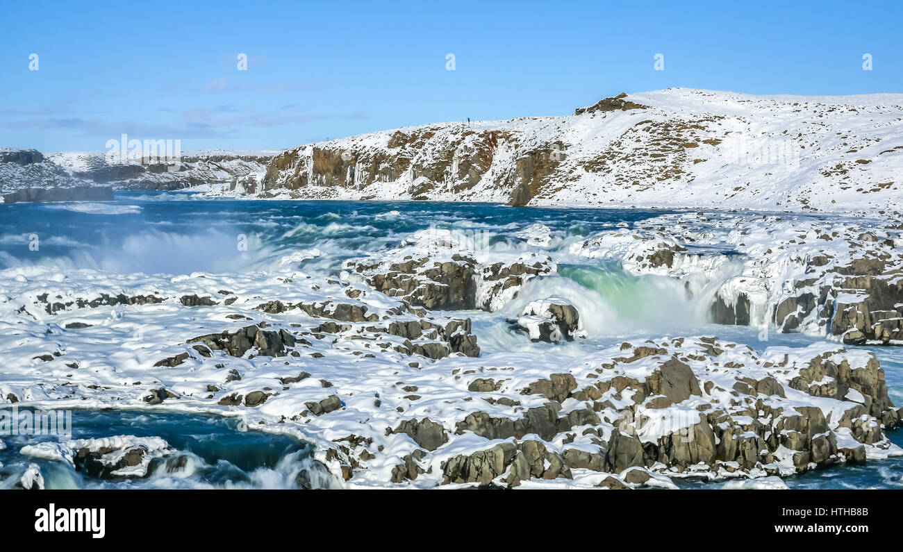 A frozen waterfall in Iceland with blue sky on winter day - Stock Image