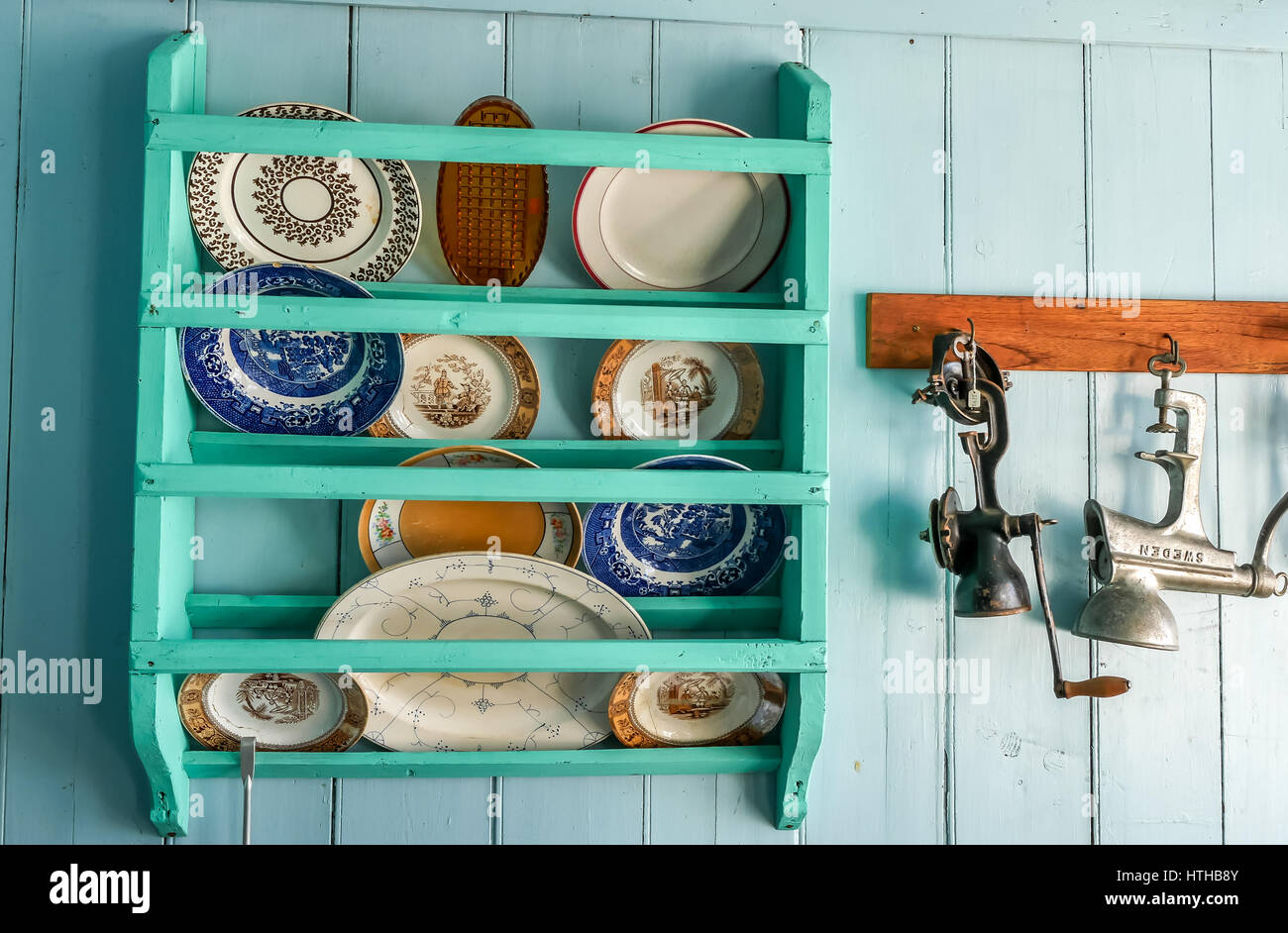 Wall with vintage kitchen equipment, plate rack and utensils in oldest wooden house in Iceland, Skogar Folk Museum - Stock Image