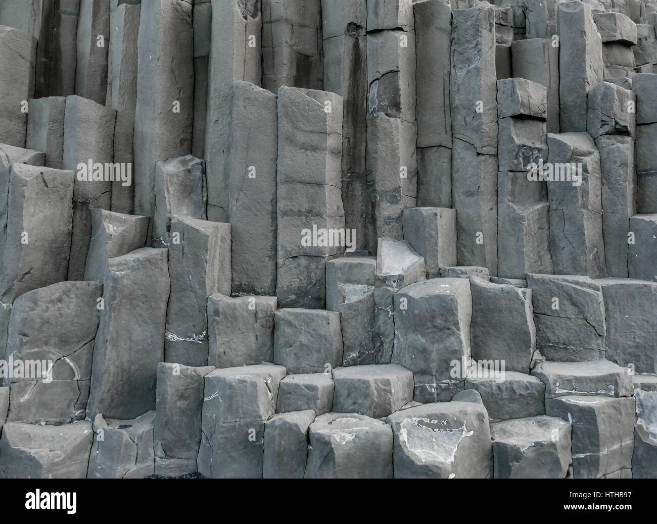 Stacks of grey volcanic hexagonal basalt volcanic rock columns, Reynisfjara, Iceland - Stock Image