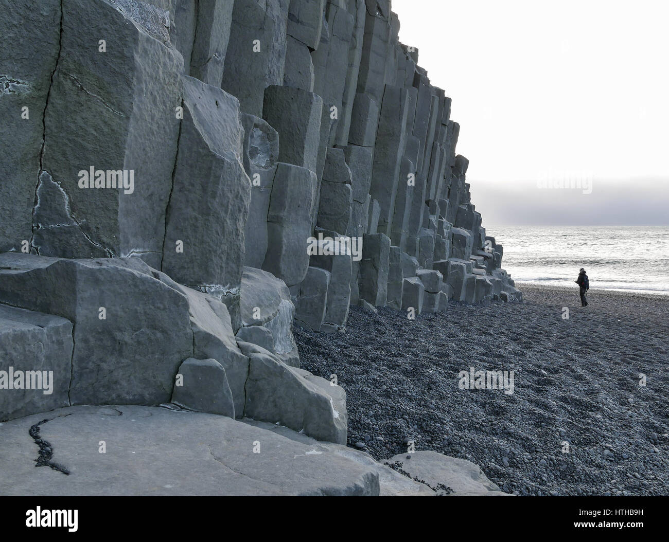 A solitary silhouette figure next to volcanic basalt hexagonal pattern cliff on black lava beach at Reynisfjara, - Stock Image