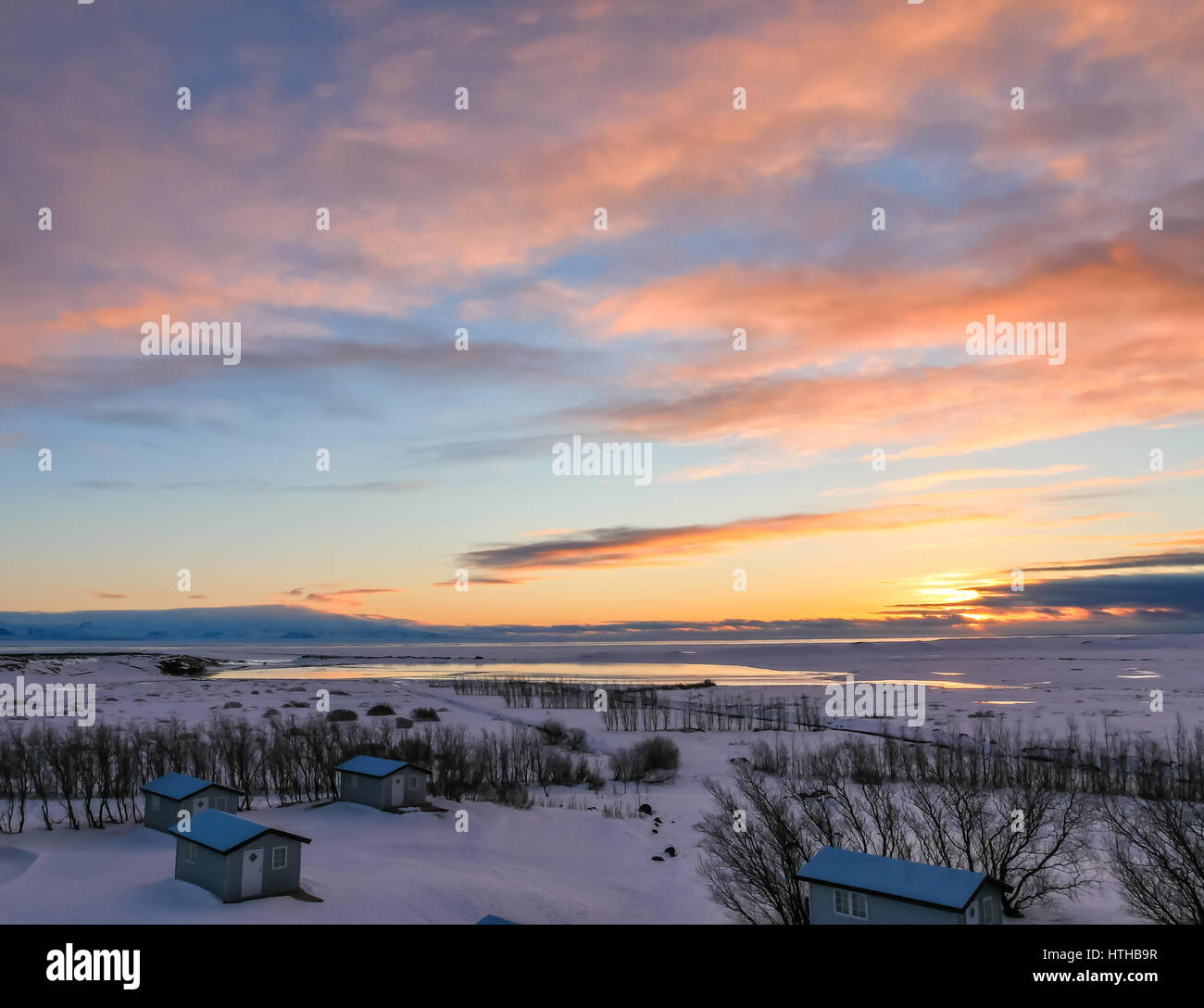 Colourful sunrise on a low horizon in winter in Iceland, with bungalow chalets in foreground - Stock Image
