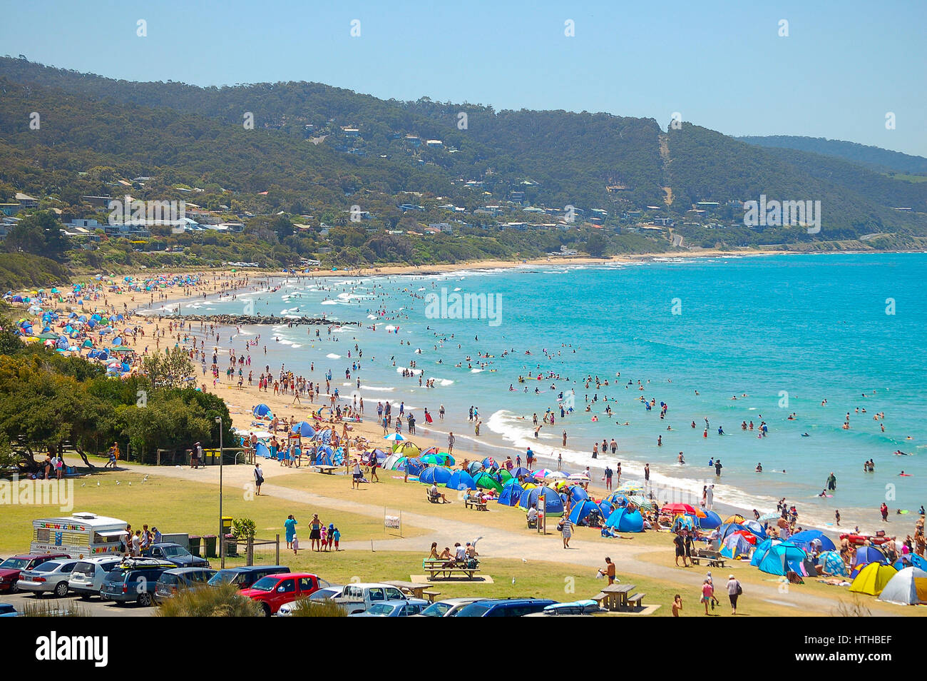 Vacationers enjoy the refreshing water in a summer heat wave on the beach of Lorne in Victoria, Australia - Stock Image