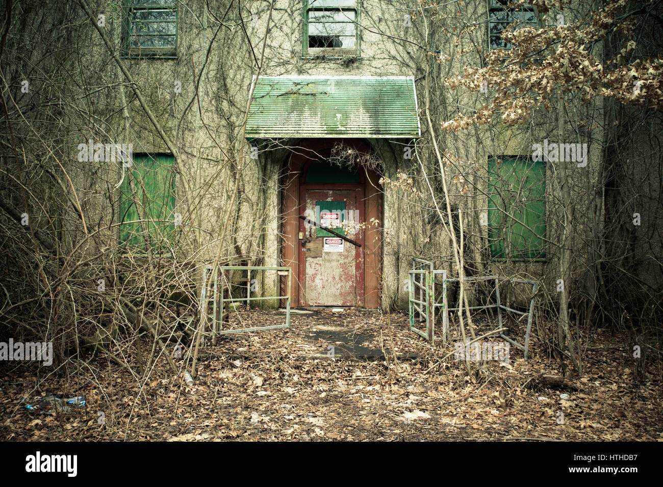 View of exterior of abandoned psychiatric hospital with asbestos warning on door - Stock Image