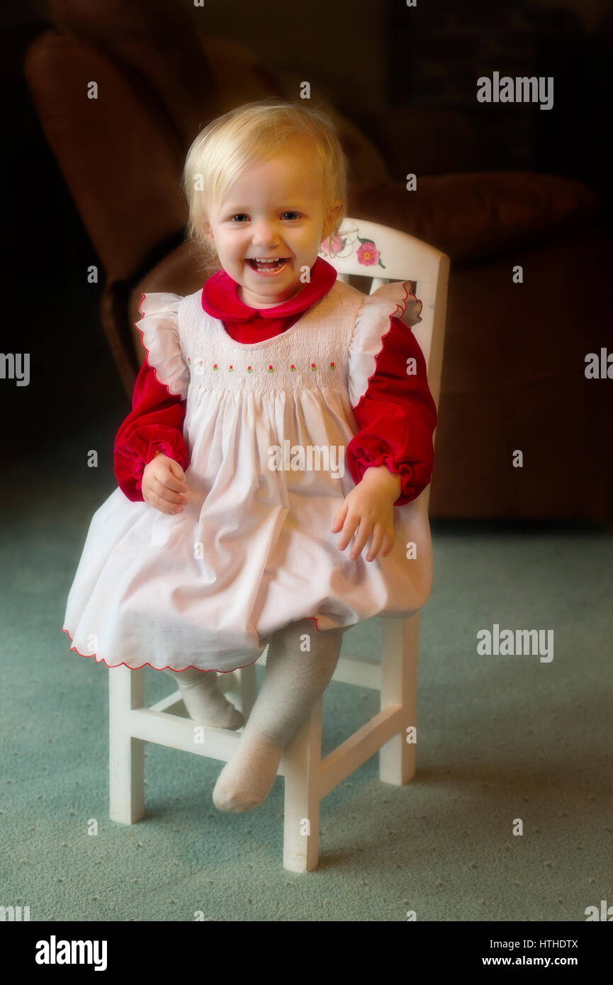 A Sweet Little Girl Sitting On A Small Child Chair