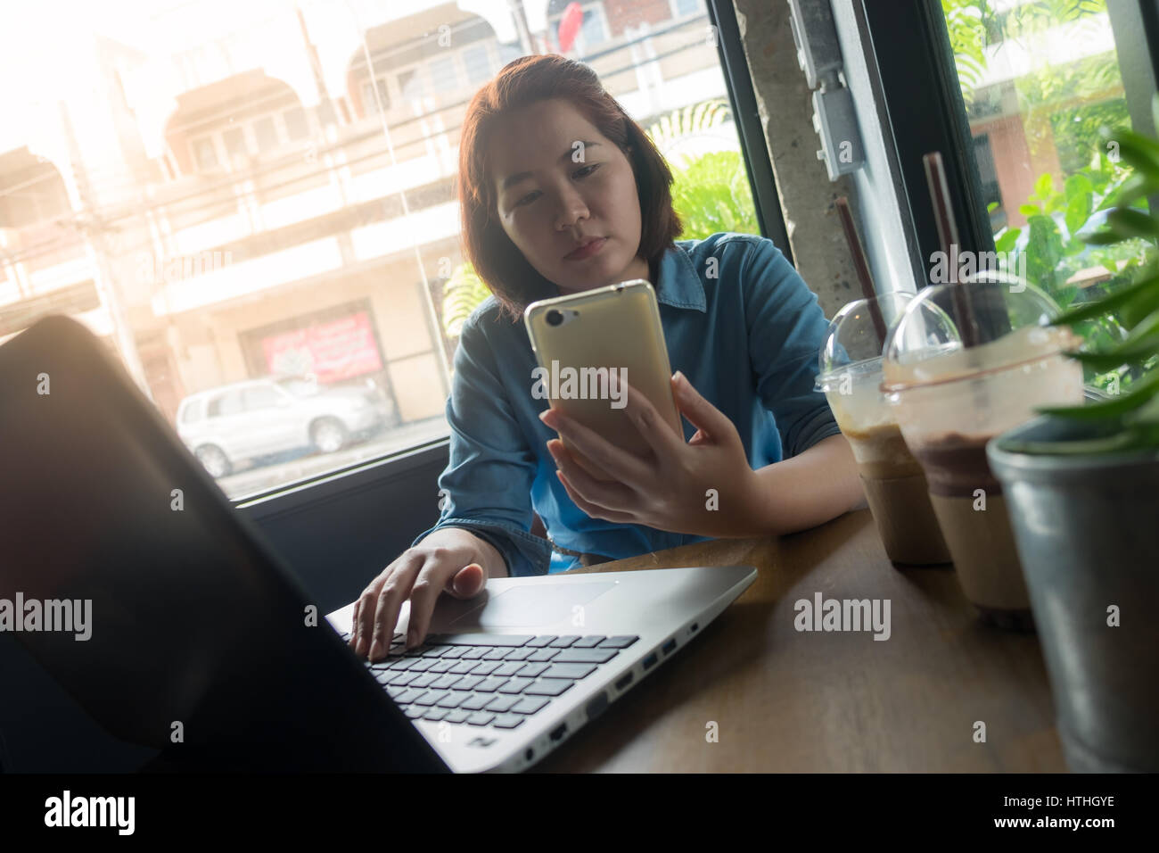 Young Asian woman using smartphone while working in coffee shop. Freelance worker on workday with laptop concept - Stock Image
