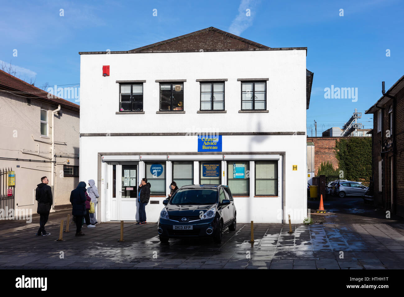 People wait outside a Citizens Advice Bureau in the early morning for it to open, Romford town Center, London, UK - Stock Image