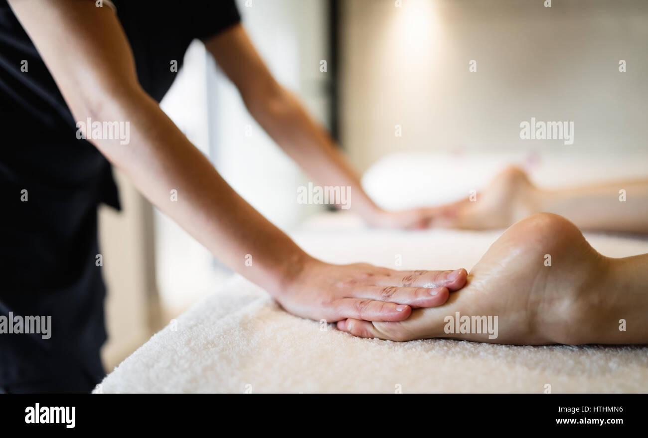 Masseuse masaging feet of person at massage salon - Stock Image