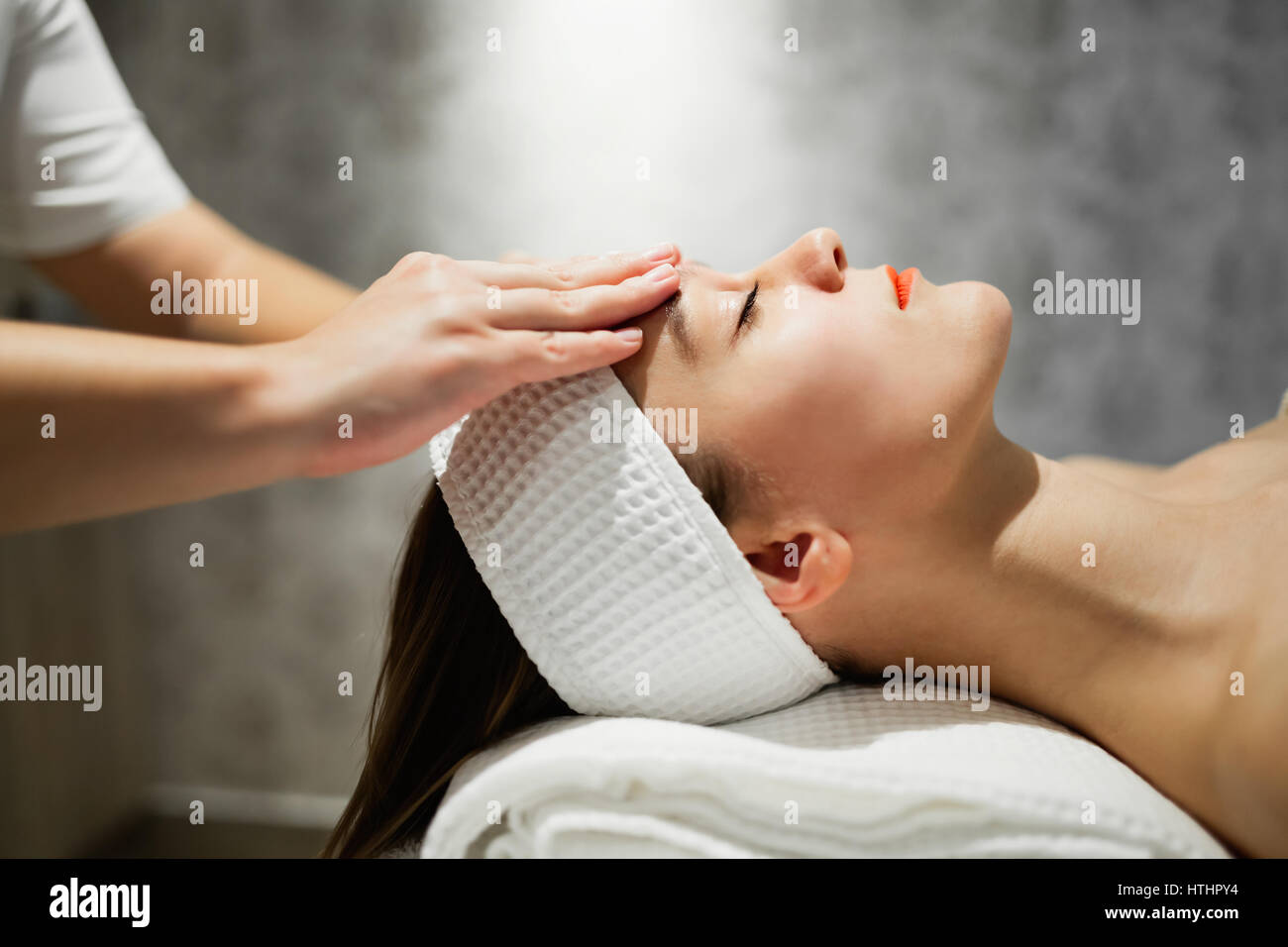 Masseuse massaging female who is relaxing at salon - Stock Image