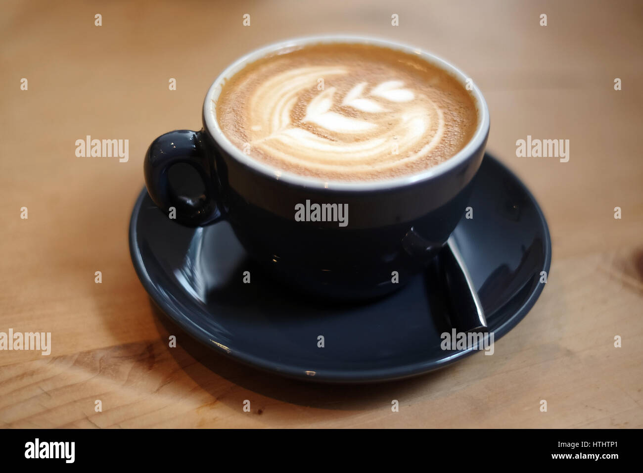 Flat white coffee, in a restaurant, on a wooden table - Stock Image