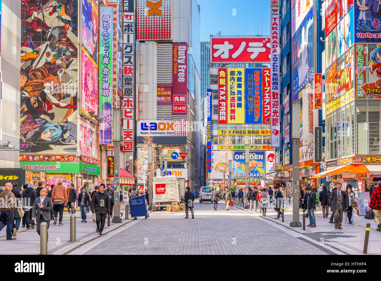 TOKYO, JAPAN - JANUARY 11, 2017: Crowds pass below colorful signs in Akihabara. The historic district electronics - Stock Image