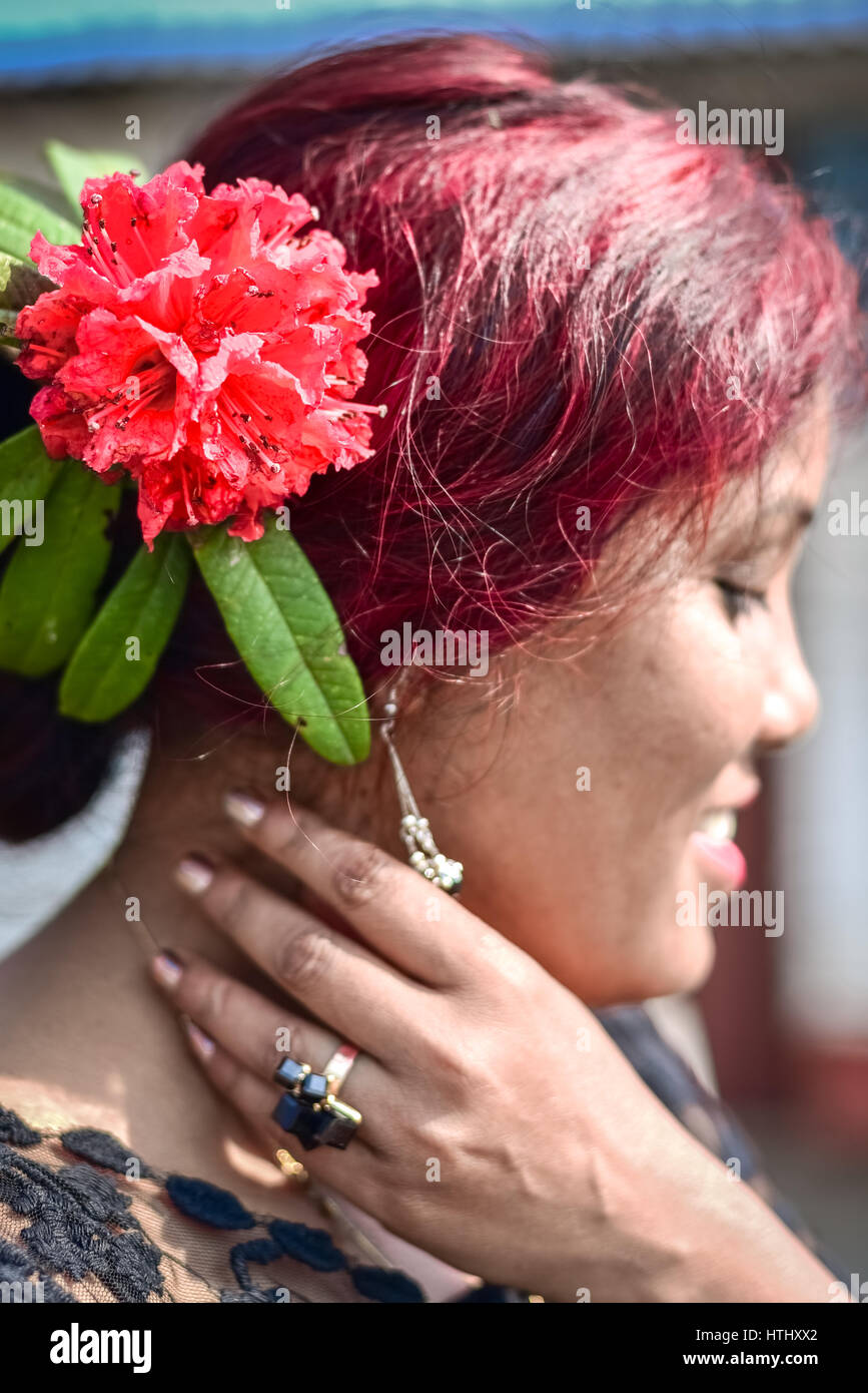 A woman wears a red rhododendron behind her ear. - Stock Image