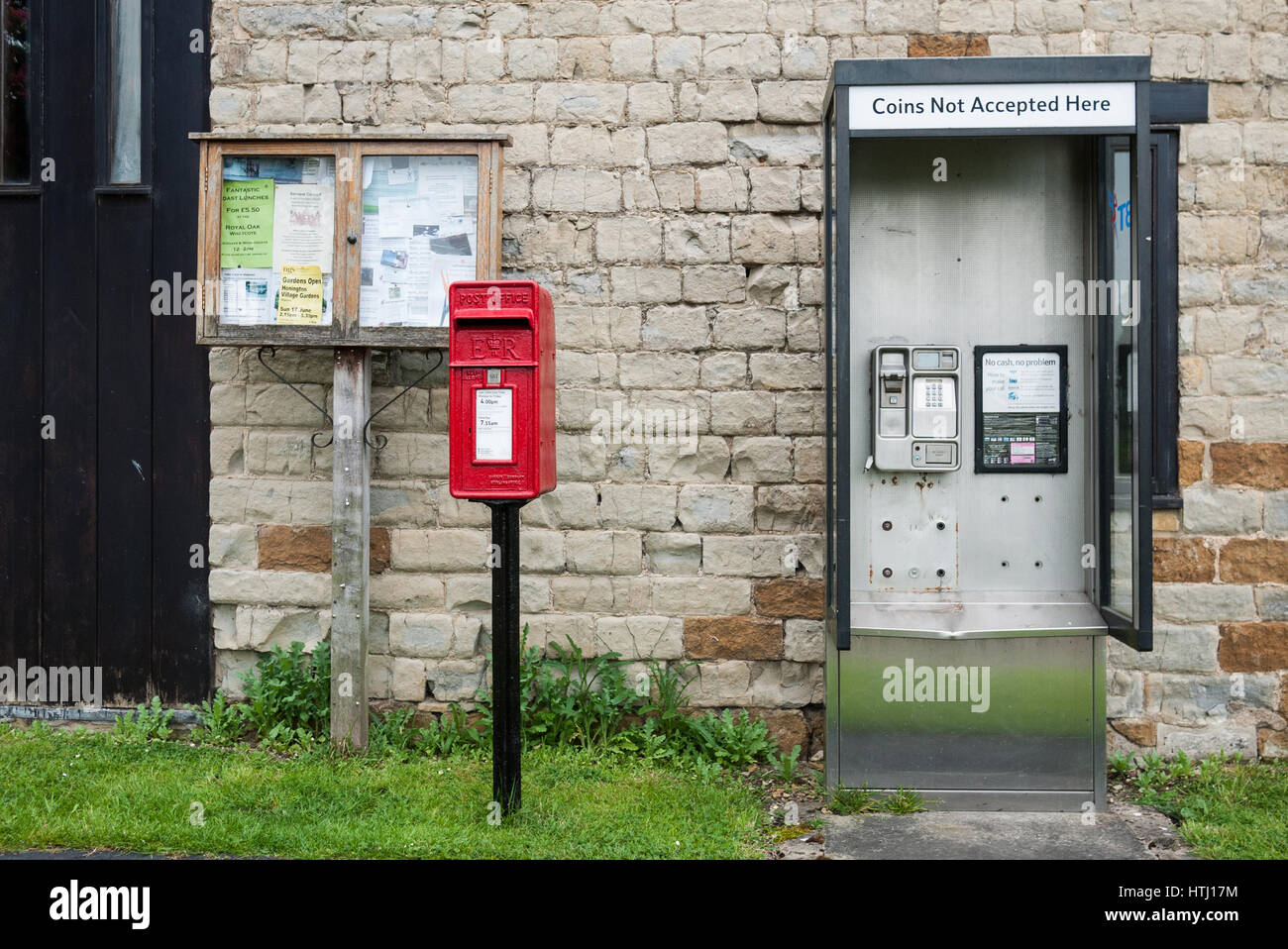 Village communications depicting notice board, post box and telephone kiosk. - Stock Image