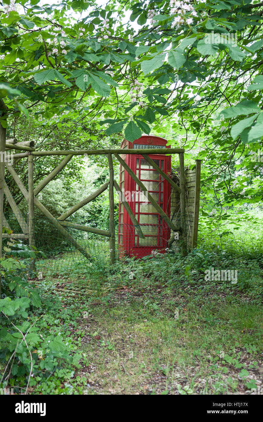 An old K6 telephone kiosk set in a garden in England. - Stock Image