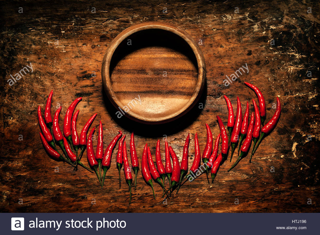 Red Hot Chili Peppers with wooden plate in over wooden rustic background with a place for an inscription. - Stock Image