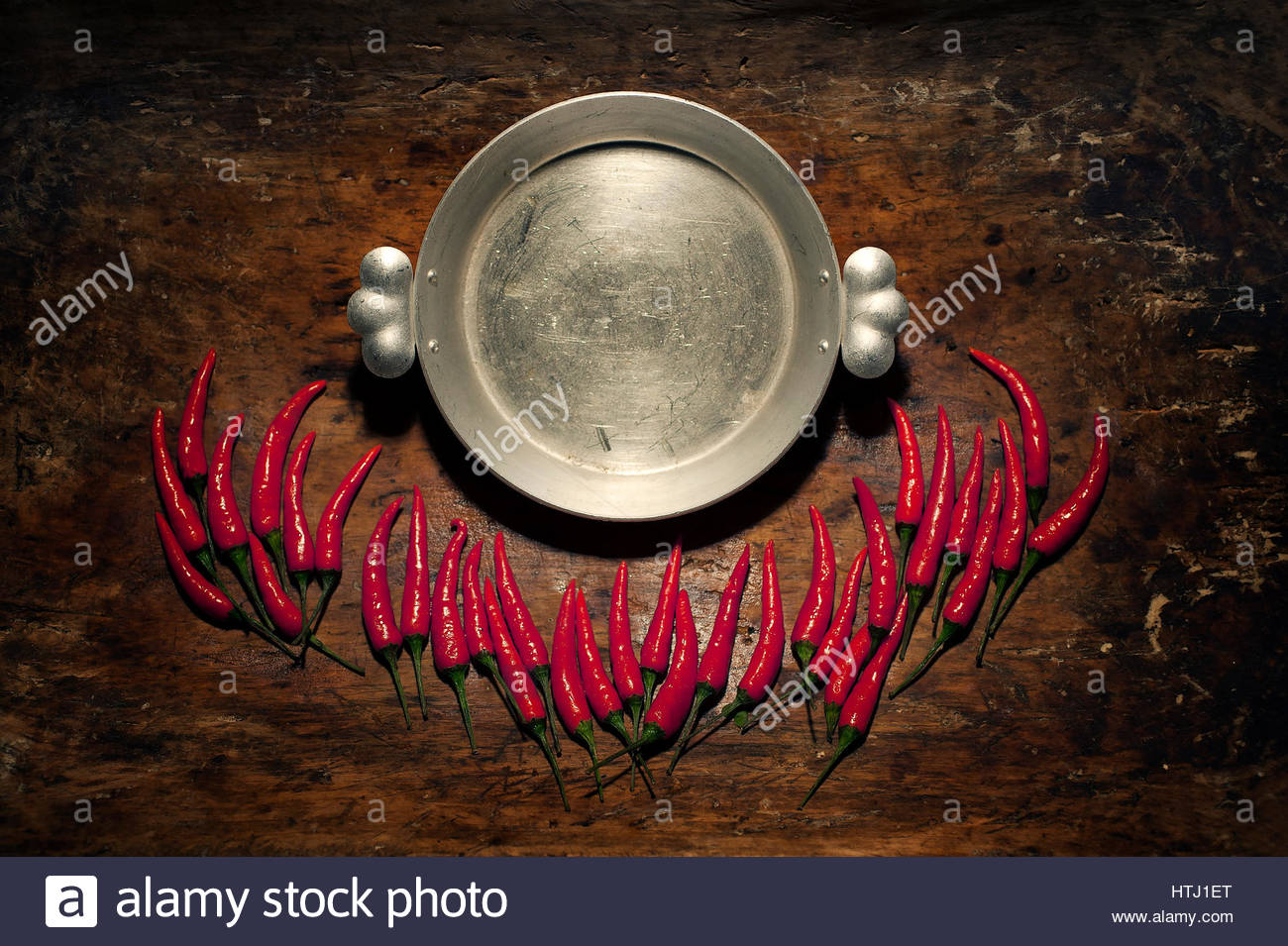 Red Hot Chili Peppers with metall plate in over wooden rustic background with a place for an inscription. Stock Photo