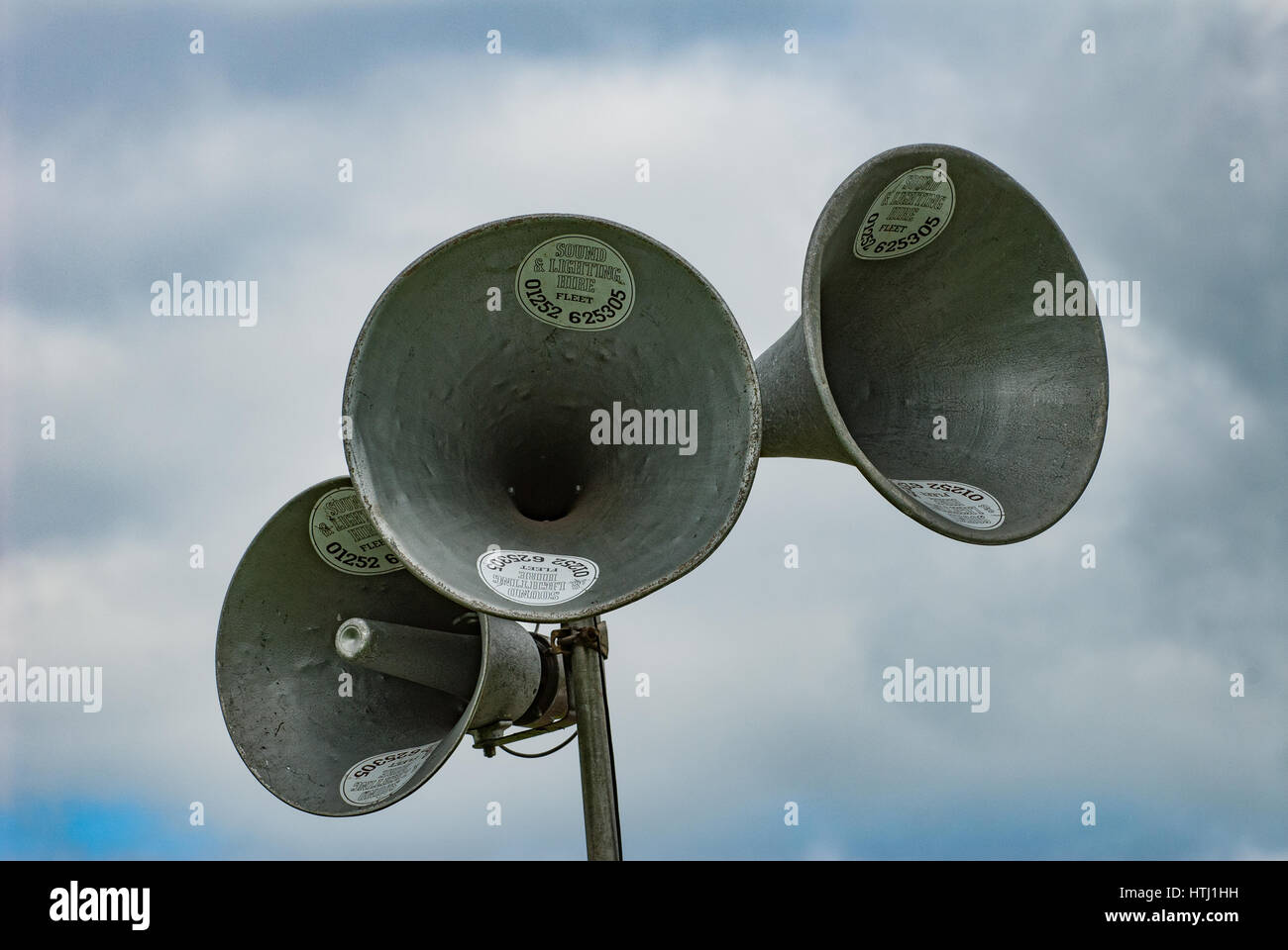 A trio of horn shaped loudspeakers with a cloudy blue sky background. - Stock Image